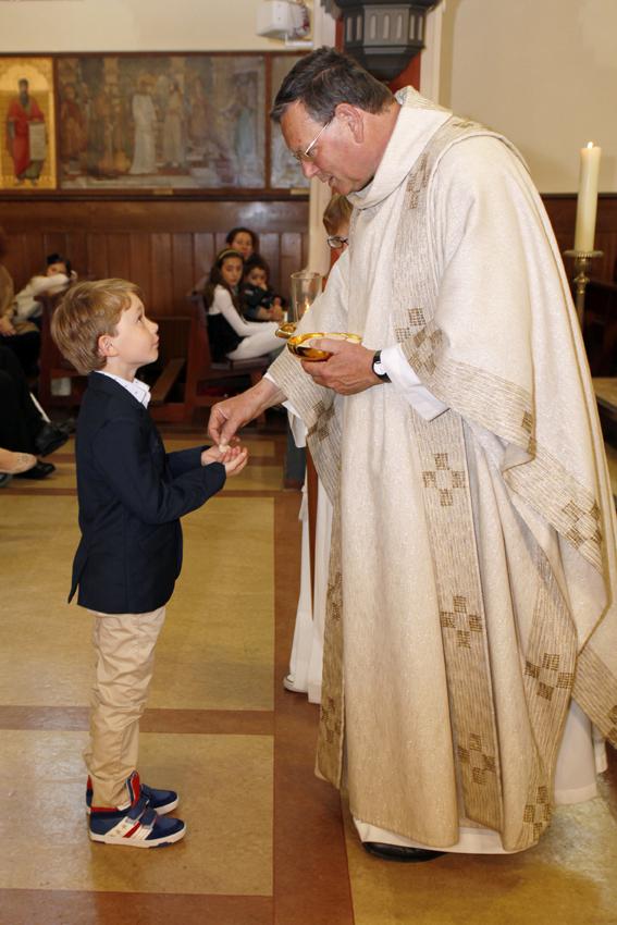 Pastoor Kees van Lent geeft de Eerste Heilige Communie aan een communicant.